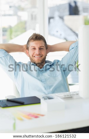 Handsome designer relaxing at his desk smiling at camera in creative office - stock photo
