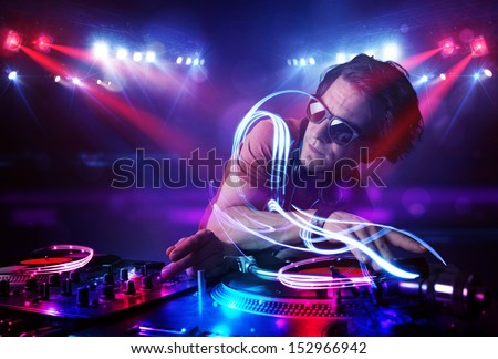 Handsome disc jockey playing music with light beam effects on stage - stock photo