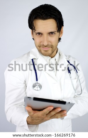 Handsome doctor smiling with tablet in hand - stock photo