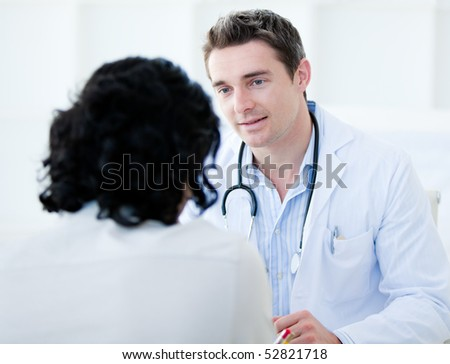 Handsome doctor talking with his patient for the annual check-up in the hospital