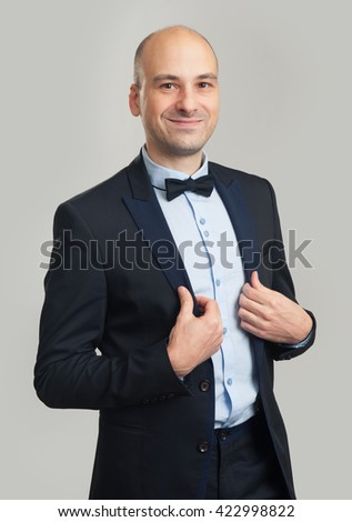 Handsome elegant bald man in suit and bow tie isolated on grey