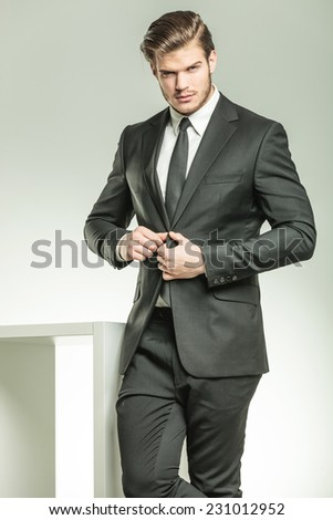 Handsome elegant business man looking at the camera while closing his jacket. - stock photo