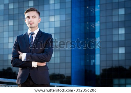 Handsome elegant businessman in front of office building
