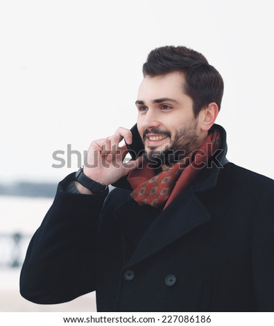 Handsome elegant man talking on the smartphone outdoors - stock photo