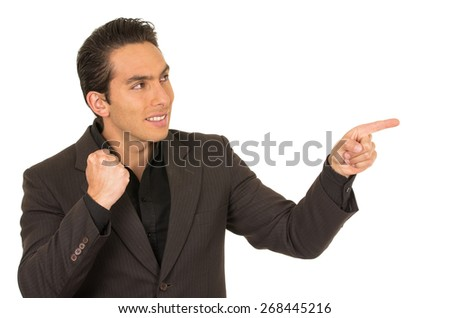 handsome elegant young latin man wearing a suit posing pointing to the side isolated on white