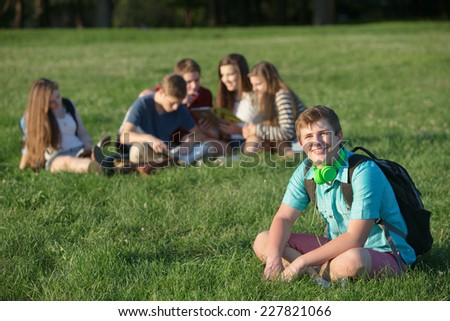 Handsome European teen male student sitting on lawn