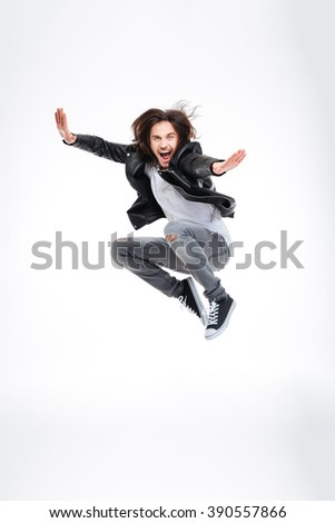 Handsome excited young man jumping and screaming over white background - stock photo