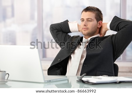 Handsome executive sitting at desk in bright office, stretching.?