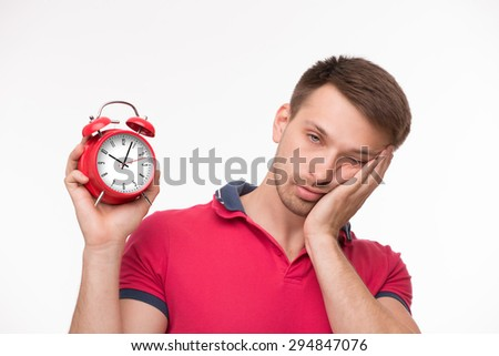 Handsome exhausted young man posing with red alarm clock. Blond man in pink T-shirt touching his cheek with left hand. - stock photo