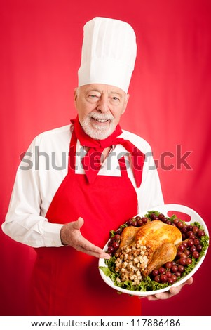 Handsome, experienced chef holding stuffed turkey dinner.  Red background. - stock photo