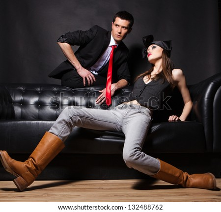 Handsome  fashion couple sitting on sofa - stock photo