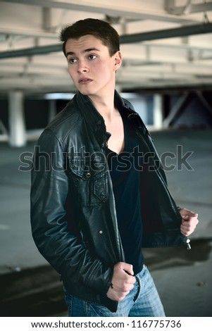 handsome fashion man in the coat standing on the car parking - stock photo