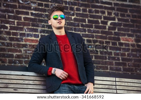 Handsome fashion man wearing casual jacket and sunglasses  standing near brick wall - stock photo