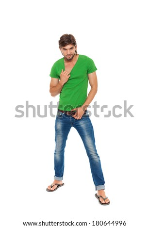 handsome fashion man wearing jeans green t-shirt, guy pulling his t shirt, full length portrait isolated over white background - stock photo