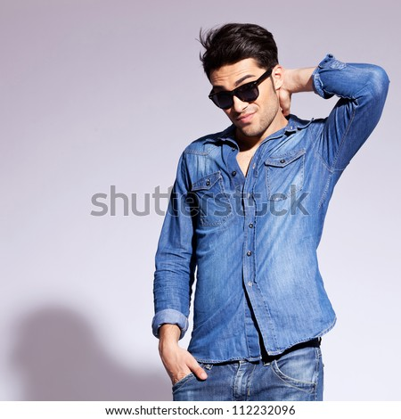 handsome fashion man wearing sunglasses thinking and scratching his head - stock photo