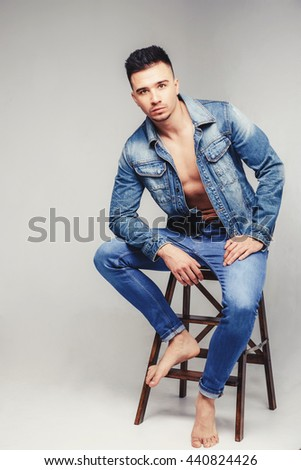 Handsome fashionable sexy sensual muscular young macho man with bare torso and stylish hair in jeans shirt - stock photo