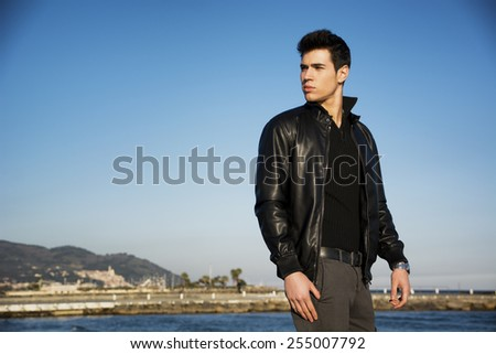 Handsome fashionable young man at the seaside along the shore overlooking the ocean or sea with his black leather jacket looking at the camera - stock photo