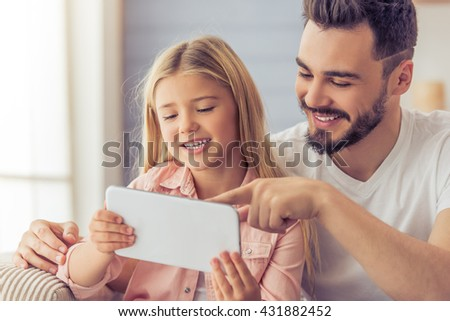 Handsome father and his cute daughter are using a tablet, talking and smiling while sitting on sofa at home - stock photo