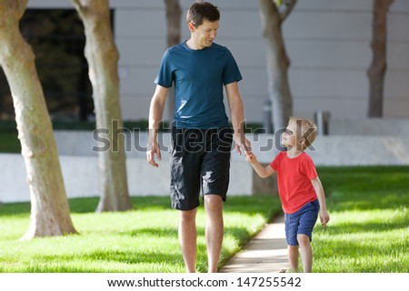 handsome father and his cute smiling son walking together outside - stock photo