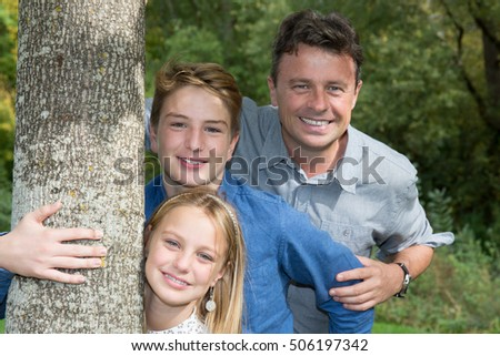Handsome Father and his daughter and son smiling outdoor