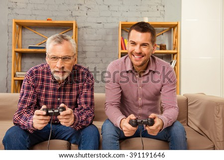 Handsome father and his  son playing video games and laughing while sitting on a sofa - stock photo