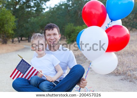 handsome father holding colorful balloons and his little son holding american flag celebrating 4th of July - stock photo