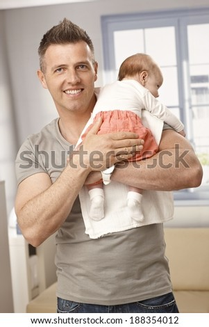Handsome father holding newborn baby girl in arms, smiling, looking at camera. - stock photo