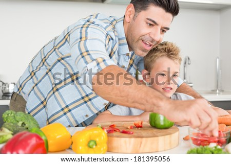 Handsome father showing his son how to prepare vegetables at home in kitchen - stock photo
