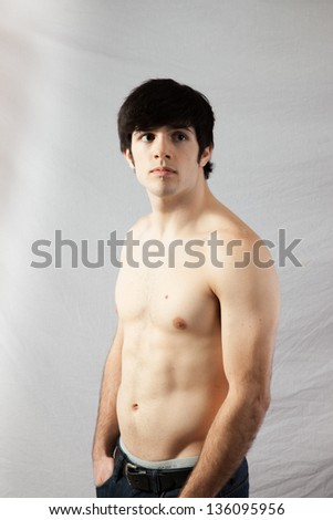 Handsome fit male standing with his shirt off, his muscles   well defined, his hands in his pockets, Looking at the camera with a serious, focused expression