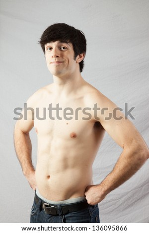 Handsome fit male standing with his shirt off, his muscles   well defined, his hands on his hips, Looking at the camera with a serious, focused expression - stock photo