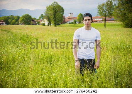 Handsome fit young man at countryside, in field or grassland, wearing white t-shirt and cap, looking at camera - stock photo
