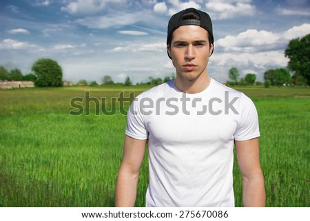 Handsome fit young man at countryside, in front of field or grassland, wearing white t-shirt and cap, looking at camera - stock photo
