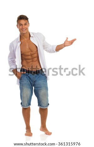 Handsome fit young man in unbuttoned white shirt and jeans shorts standing barefoot holding open hand, showing something and looking at camera. Full length studio shot isolated on white.