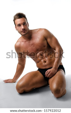 Handsome, fit, young man on his knees showing muscular naked body - stock photo