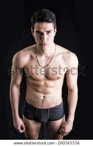 Handsome, fit young man wearing only underwear standing on black background, looking at camera - stock photo