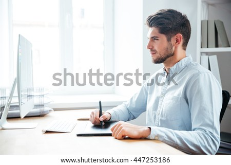 Handsome focused young man designer working using computer and graphic tablet in office