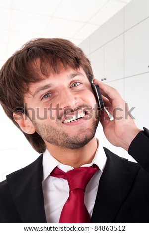 Handsome friendly businessman using a cell phone