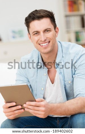 Handsome friendly young man holding a tablet sitting on a sofa at home looking at the camera with a smile