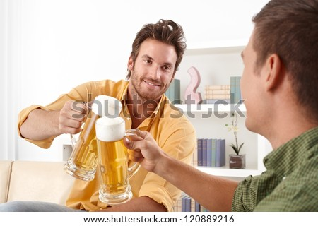Handsome friends clinking with beer glass, smiling.