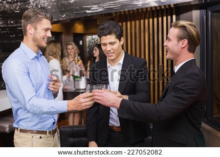 Handsome friends having a drink together at the bar