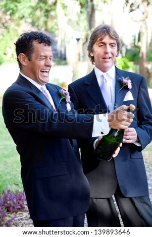 Handsome gay couple at their wedding, opening a bottle of champagne.