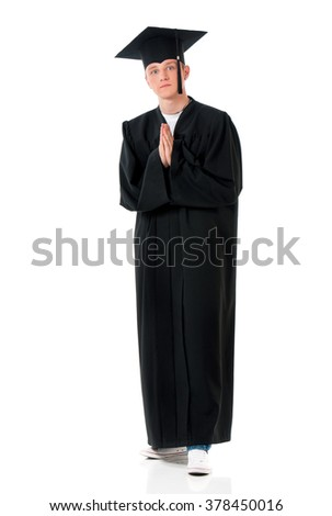 Handsome graduate guy student in mantle - hands folded in prayer, isolated on white background