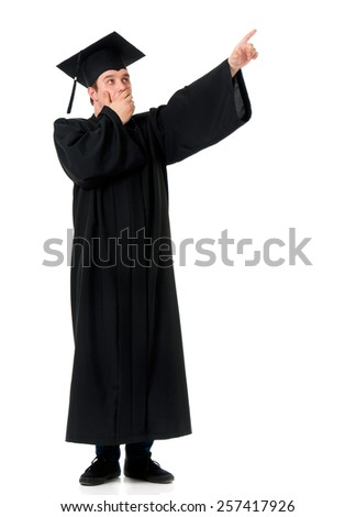 Handsome graduate guy student in mantle showing something, isolated on white background - stock photo