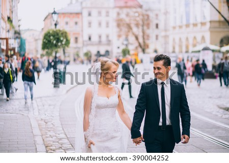 Handsome groom and beautiful bride walking on old european street architecture