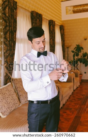 Handsome groom getting dressed, putting his watch in his wedding day - stock photo