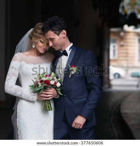 Handsome groom hugging happy bride in french street - stock photo