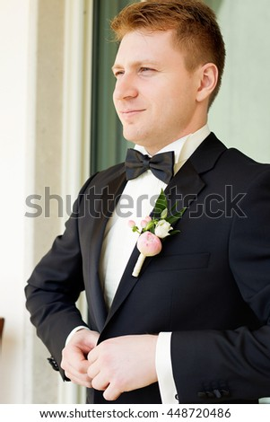 handsome groom in suit with bow tie