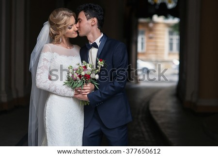 Handsome groom kissing happy bride in french street - stock photo