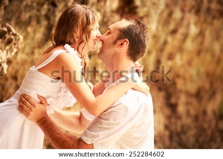 handsome groom stands on his knees and kiss blonde bride against rock at sand beach - stock photo