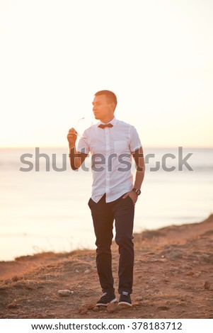 Handsome groom walking on cliff near sea on sunset